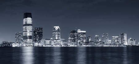 Jersey City skyline with skyscrapers at night black and white over Hudson River viewed from New York City Manhattan downtown. photo