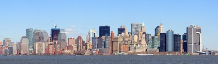 New York City Manhattan downtown district skyline panorama with skyscrapers over river with blue clear sky.  photo