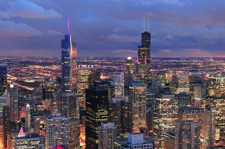 Chicago: Chicago skyline panorama aerial view with skyscrapers with cloudy  sky at dusk.