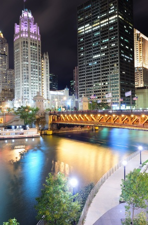 Chicago River Walk with urban skyscrapers and bridge illuminated with lights and water reflection at night.