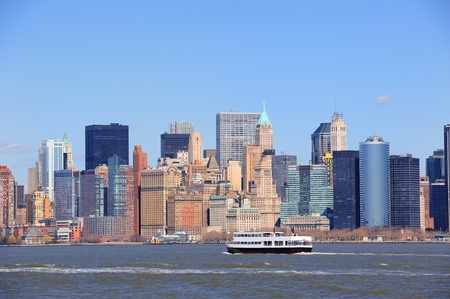Urban skyscrapers and boat from New York City Manhattan downtown over river. photo