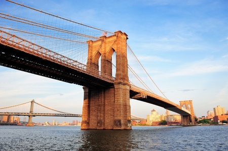 bridges: Brooklyn Bridge over East River viewed from New York City Lower Manhattan waterfront at sunset. Stock Photo