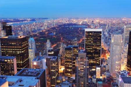 New York City skyline aerial view at dusk with central park and skyscrapers of midtown Manhattan lit by lights.