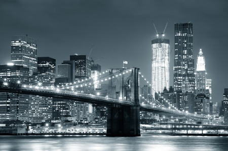 New York City Brooklyn Bridge black and white with downtown skyline over East River. Editorial