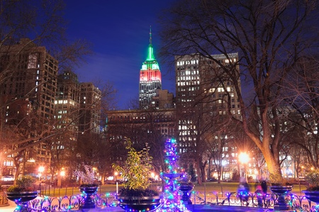 New York City Madison Square park view with Christmas color lights and Manhattan skyscrapers.