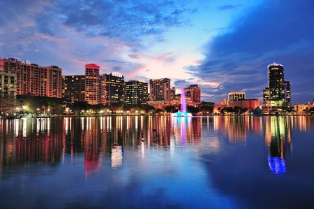 city park skyline: Orlando downtown skyline over Lake Eola at dusk with urban skyscrapers and lights.