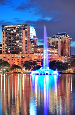 Fountain closeup with Orlando downtown skyline over Lake Eola at dusk with urban skyscrapers and lights.