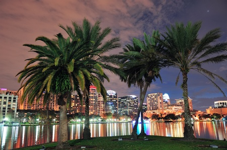 lake district: Oconut tree and Orlando downtown skyline over Lake Eola at dusk with urban skyscrapers and lights. Stock Photo