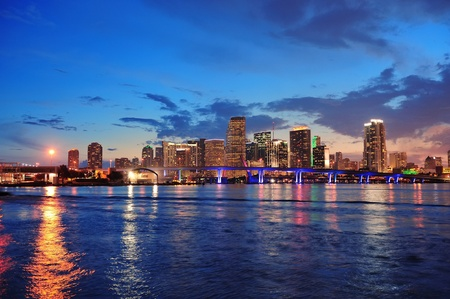 Miami city skyline panorama at dusk with urban skyscrapers and bridge over sea with reflection photo