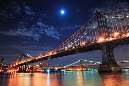 moon  metropolis: Brooklyn Bridge and Manhattan Bridge over East River at night with moon in New York City Manhattan with lights and reflections.