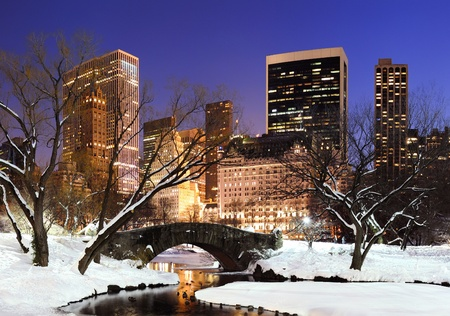 New York City Manhattan Central Park panorama in winter with snow, bridge; freezing lake and skyscrapers at dusk  photo