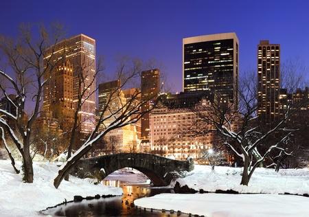 january sunrise: Nueva York Central Park de Manhattan panorama en invierno con la nieve, el puente; lago helado y los rascacielos al atardecer