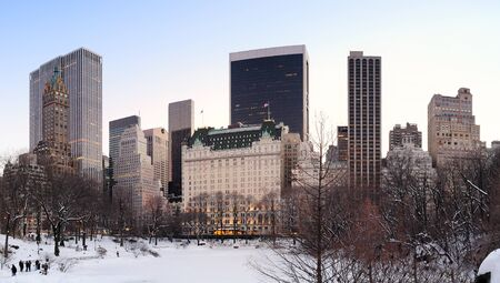 New York City Manhattan Central Park panorama in winter with snow, freezing lake and skyscrapers at dusk  photo