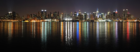 weehawken: New York City Manhattan midtown skyline panorama at night with lights reflection over Hudson River  Stock Photo