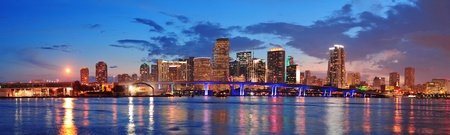 miami sunset: Miami city skyline panorama at dusk with urban skyscrapers and bridge over sea with reflection