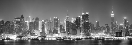 new york city times square: New York City Manhattan midtown skyline black and white at night with skyscrapers lit over Hudson River with reflections
