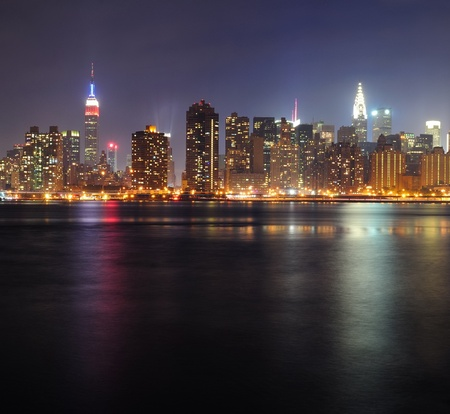 New York City Manhattan midtown panorama at night with skyscrapers illuminated over east river photo