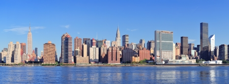 Manhattan midtown skyline panorama over East River with urban skyscrapers and blue sky in New York City photo