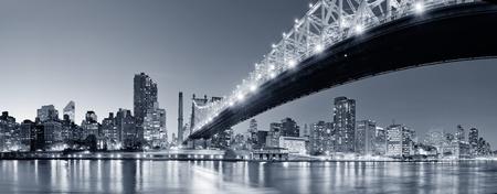 Queensboro Bridge über New York City East River Schwarz-Weiß-Fluss in der Nacht mit Reflexionen und Midtown Manhattan Skyline beleuchtet