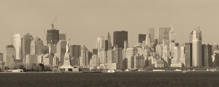 New York City lower Manhattan skyline black and white with Statue of Liberty and urban city skyline over river panorama view