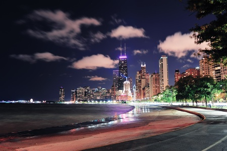 Chicago city urban skyscraper at night at downtown lakefront illuminated with Lake Michigan and water reflection viewed from North Avenue Beach.