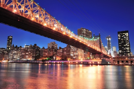 Queensboro Bridge over New York City East River at sunset with river reflections and midtown Manhattan skyline illuminated.  Stock Photo - 12993090