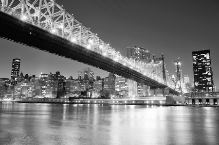 east river: Queensboro Bridge over New York City East River black and white at night with river reflections and midtown Manhattan skyline illuminated.