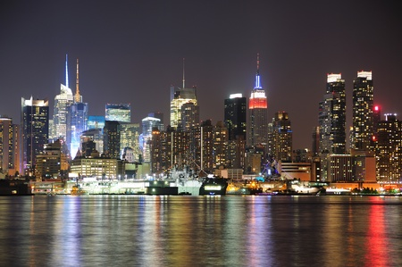 New York City Manhattan midtown skyline at night with lights reflection over Hudson River viewed from New Jersey Weehawken waterfront. Editorial