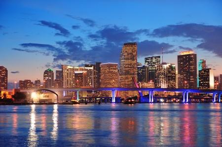 Miami city panorama panorama za soumraku s městskými mrakodrapy a most přes moře s odrazem