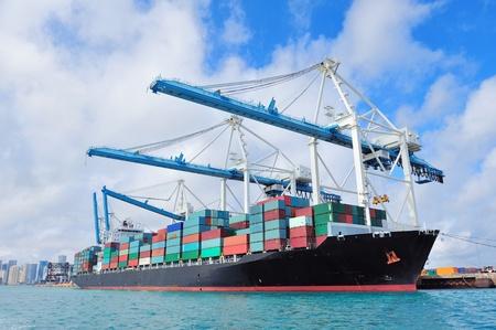 containerschip: Cargo schip op Miami haven met kraan en blauwe lucht boven zee. Redactioneel