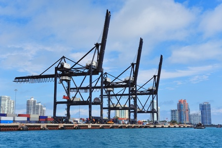 Crane at Miami harbor with blue sky over sea.