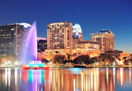 florida landscape: Orlando downtown skyline panorama over Lake Eola at night with urban skyscrapers, fountain and clear sky.