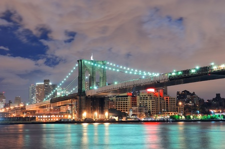 east river: Brooklyn Bridge over East River at night in New York City Manhattan with lights and reflections. Editorial