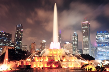 Chicago skyline with skyscrapers and Buckingham fountain in Grant Park at night lit by colorful lights.