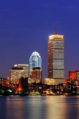 Boston city skyline at dusk with Prudential Tower and urban skyscrapers over Charles River with lights and reflections