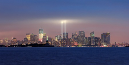 september 11: New York City Manhattan downtown skyline panorama at night with statue of liberty and light beams in memory of September 11 viewed from New Jersey waterfront