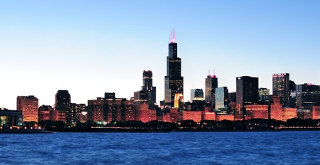 lakefront: Chicago city downtown urban skyline panorama at dusk with skyscrapers over Lake Michigan with clear blue sky.