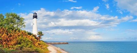 Cape Florida Światło latarni przy Oceanie Atlantyckim i palmy na plaży w Miami, błękitne niebo i chmury. Zdjęcie Seryjne
