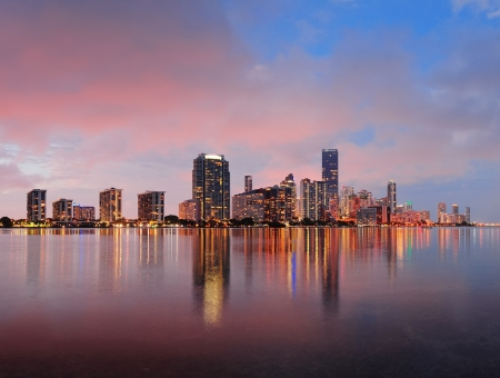Miami city skyline panorama at dusk with urban skyscrapers over sea with reflection Banco de Imagens