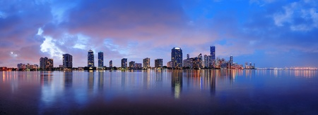 miami sunset: Miami city skyline panorama at dusk with urban skyscrapers over sea with reflection Editorial