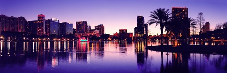 lake district: Orlando downtown skyline panorama silhouette over Lake Eola at dusk with urban skyscrapers. Editorial
