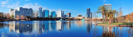 city park skyline: Orlando Lake Eola in the morning with urban skyscrapers and clear blue sky.