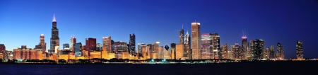 skyline: Chicago city downtown urban skyline panorama at dusk with skyscrapers over Lake Michigan with clear blue sky.