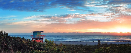 panoramic beach: Miami South Beach sunrise panorama with lifeguard tower and coastline with colorful cloud and blue sky.