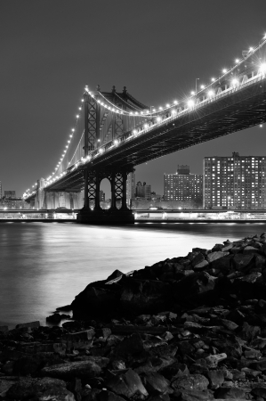 east river: New York City Manhattan Bridge closeup black and white with downtown skyline over East River.
