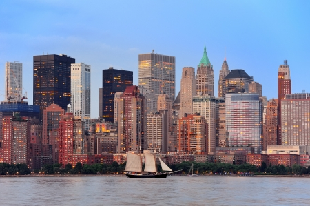 New York City Manhattan downtown skyline with boat at sunset over Hudson River panorama photo
