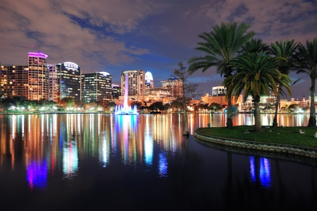 lake district: Orlando downtown skyline over Lake Eola at dusk with urban skyscrapers and lights.