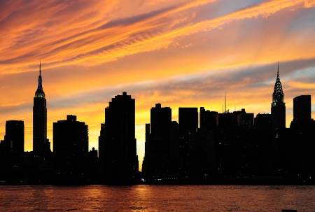 east river: New York City Manhattan midtown silhouette panorama at sunset with skyscrapers and colorful sky over east river Stock Photo