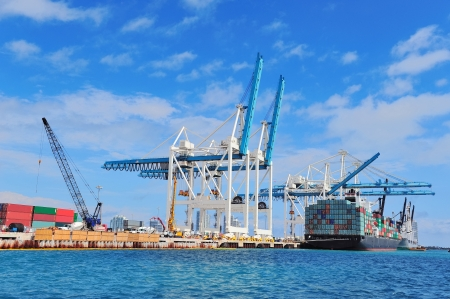 Cargo ship at Miami harbor with crane and blue sky over sea. photo
