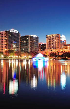 Orlando downtown skyline panorama over Lake Eola at night with urban skyscrapers, fountain and clear sky. photo